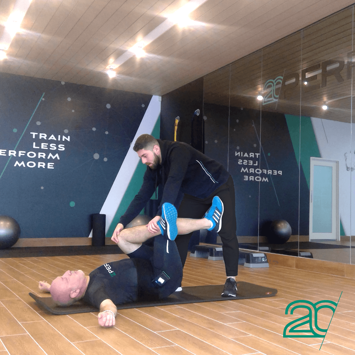 Man Getting Stretched by a Personal Trainer Using 20PerFit's EMS Technology