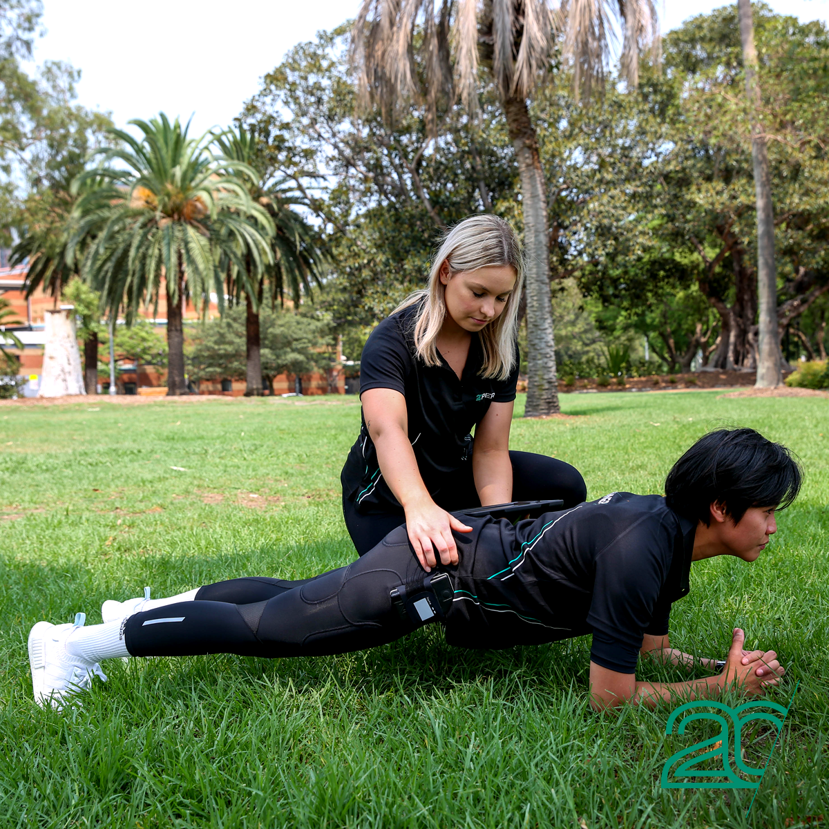 Woman Doing Core Exercises with a Personal Trainer Using 20PerFit's EMS Technology