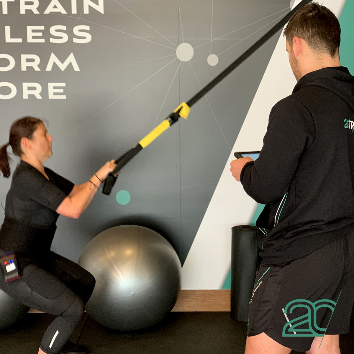 Woman Doing Squats Using EMS with the Help of a 20PerFit Personal Trainer